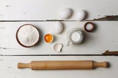 Wypiekowy tło Kulinarni składniki dla drożdżowego ciasta, ciasto, jajka, mąka i mleko na białym nieociosanym drewnie, Odgórny wid Zdjęcie Royalty Free