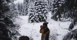 Wyposażający młody człowiek turystyczny podróżujący przez ciężkiej zimy po środku śnieżnego lasu go cieszy się czasu pić zbiory