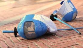 Wyposażenie szermiercza maska i foliowy odpoczywać na ziemi po Obraz Stock