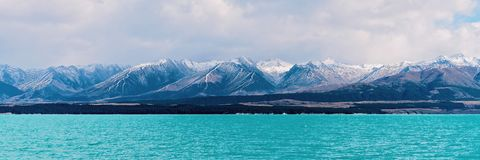 Wyróżniający Błękitne Wody jezioro Z śniegi Nakrywającymi Halnymi Alps W tle zdjęcia stock