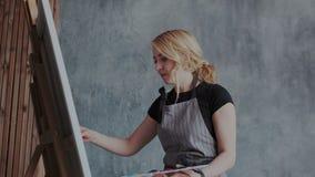 Wyraża twój twórczość Pozytywny młoda kobieta rysunek na sztaludze podczas gdy cieszący się jej hobby Barwiąca farba stosuje