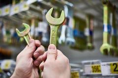 Wyrwania w rękach na tło ścianie z narzędziem w sklepie Fotografia Stock