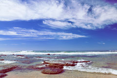 Wyrzucać na brzeg blisko Mosselbay Południowa Afryka podczas ranku światła słonecznego pod chmurnym niebem Fotografia Stock