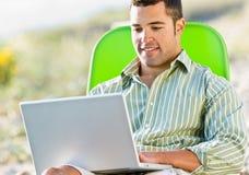 wyrzucać na brzeg laptopu mężczyzna używać Zdjęcia Royalty Free