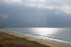 Wyrzucać na brzeg pod jaskrawym słońcem na oceanie Piękne podeszczowe chmury i świecenie na powierzchni woda obraz stock