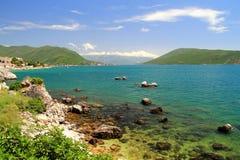 Wyrzucać na brzeg z skałami w morzu i górami w odległości pięknymi, malowniczymi, Zdjęcie Royalty Free
