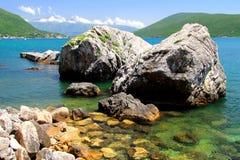 Wyrzucać na brzeg z skałami w morzu i górami w odległości pięknymi, malowniczymi, Zdjęcia Royalty Free