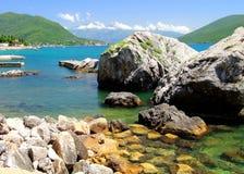 Wyrzucać na brzeg z skałami w morzu i górami w odległości pięknymi, malowniczymi, Obrazy Royalty Free