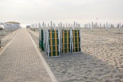 Wyrzucać na brzeg z zamkniętymi parasolami, sunbeds, słońc loungers i parasole, wczesny poranek w Sottomarina, Włochy, Europa zdjęcia royalty free