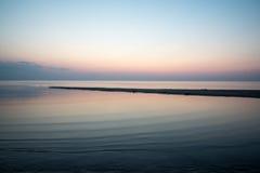 Wyrzucać na brzeg po zmierzchu z piaskiem i chmurami Zdjęcie Royalty Free