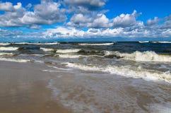 Wyrzucać na brzeg z fala i chmurami na niebieskim niebie Zdjęcia Stock