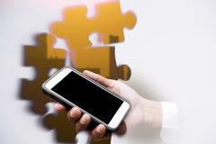 Wyrzynarki łamigłówki dwoisty ujawnienie z ręka chwyta telefonem komórkowym Fotografia Stock