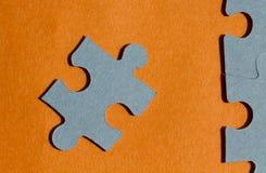 Wyrzynarki łamigłówki kawałki na jaskrawym pomarańczowym tle Obraz Royalty Free