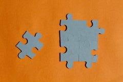 Wyrzynarki łamigłówki kawałki na pomarańczowym tle Fotografia Royalty Free