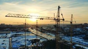 Wysocy żurawie rusza się podczas gdy pracujący na budowie w mieście zbiory