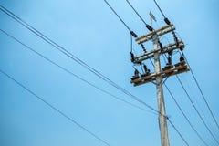 Wysocy woltaży kable, equipments na słupie z jasnym niebieskiego nieba tłem i obrazy stock