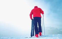 Wysoka narciarka w czerwonym czarnym kombinezonie z dużym foots z narciarskimi słupami w jego rękach i obraz stock