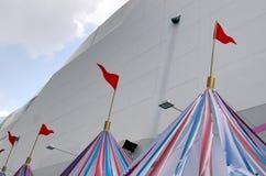 Wysoka sekcja Kolorowi Pasiaści namioty z czerwonymi flagami przy karnawałem fotografia royalty free