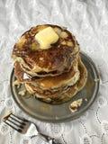 Wysoka sterta hotcakes z rozciekłym masłem i syropem na białej pościeli zdjęcie stock