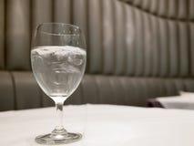 Wysoka szklana pełnia wodą i lód stawiającym dalej whit powierzchni stołem w restauraci Zdjęcia Royalty Free
