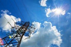 Wysoka woltaż linia, słońce w niebie i Zdjęcia Stock
