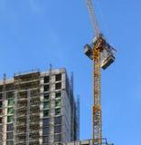 Wysoki żółty dźwigowy działanie na wielkim multistory budynku w budowie obraz stock