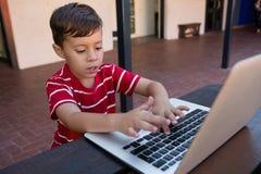 Wysoki agle widok chłopiec używa cyfrowego laptop przy stołem podczas gdy siedzący Obrazy Royalty Free