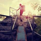 Wysoki backpacker chwyta poręcz na skale Pogodny brzask w skałach Wycieczkowicz z dużym plecakiem, baseball nakrętką, zmrok spodn Fotografia Stock