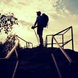 Wysoki backpacker z słupami w ręce Pogodny wiosna brzask w skalistych górach Wycieczkowicz z plecakiem, baseball nakrętką, spodni Fotografia Stock