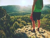 Wysoki biegacz w zielonym singlet i czerni dyszy Nieustraszenie chłopiec przy krawędzią zdjęcie stock