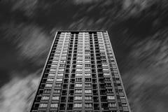 Wysoki budynek i bieg chmurniejemy w czarny i biały dla tła Obrazy Stock
