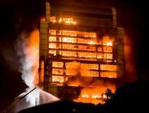 Wysoki budynek na pożarniczych, dużych ogieniach burnning/ Obraz Stock