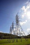 Wysoki elektryczny przekaz góruje przy hydroelektryczną tamą fotografia stock