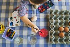 Wysoki kąt Na Little Boy używać Wodnych kolory Malować Wielkanocnych jajka W Domu zdjęcie stock