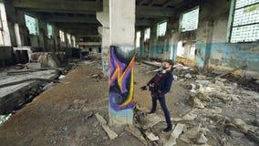 Wysoki kąta strzał młody miastowy artysta dekoruje wysoką kolumnę w starym uszkadzającym budynku z abstrakcjonistycznym wizerunki zdjęcie wideo