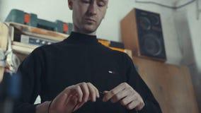 Wysoki mężczyzna w czarnym turtleneck pracuje z drutami i electrics Fotografia Royalty Free