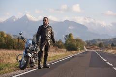 Wysoki sportowy rowerzysta w czarnej rzemiennej ubraniowej pozycji przy nowożytnym potężnym szybkościowym motocyklem zdjęcie stock