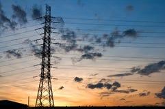 Wysoki woltaż elektryczności pilon na zmierzchu zdjęcia stock