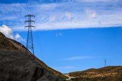 Wysoki woltaż elektryczności systemu dystrybucji władzy metalu ramy struktury wierza w krajobrazowym obszarze wiejskim z niebiesk Obraz Stock