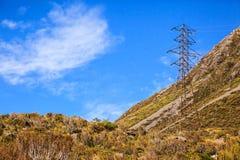 Wysoki woltaż elektryczności systemu dystrybucji władzy metalu ramy struktury wierza w krajobrazowym obszarze wiejskim z niebiesk Zdjęcie Stock