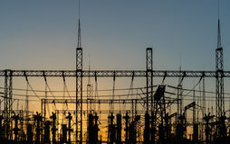 Wysoki woltaż władzy wierza i sylwetek linii energetycznych zmierzch Zdjęcia Stock