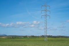 Wysoki woltażu wierza, kabel i wykładamy w wsi pod niebieskim niebem Zdjęcie Royalty Free
