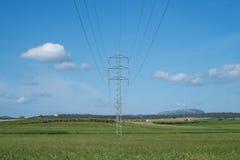 Wysoki woltażu wierza, kabel i wykładamy w wsi pod niebieskim niebem Zdjęcia Royalty Free