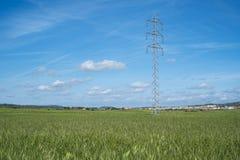 Wysoki woltażu wierza, kabel i wykładamy w wsi pod niebieskim niebem Fotografia Royalty Free