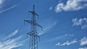 Wysoki woltażu wierza z chmurnego nieba tłem, linia energetyczna, czasu upływ zbiory
