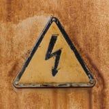 Wysoki woltażu znak na ośniedziałej stali powierzchni Obrazy Stock