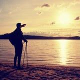 Wysoki wycieczkowicz w ciemnym sportswear z słupami i sporty plecak na plaży cieszymy się zmierzch przy horyzontem Magiczny jesie Fotografia Stock