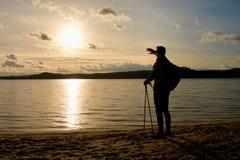 Wysoki wycieczkowicz w ciemnym sportswear z słupami i sporty plecak na plaży cieszymy się zmierzch przy horyzontem Magiczny jesie Obraz Royalty Free