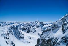 Wysokie góry śnieżne w zimy blusky tle Zdjęcie Stock