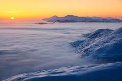 Wysokie góry w mgle, ranku niebo są oświecają z pomarańcze barwiącym światłem w zima dniu Fantastyczna zimy sceneria Obraz Stock